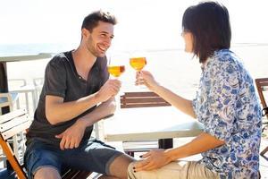glückliches Paar, das einen Spritz am Meer trinkt foto