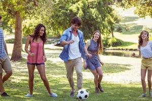 glückliche Freunde im Park mit Fußball foto