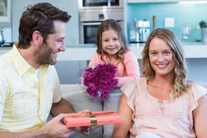 Vater und Tochter überraschen Mutter mit Geschenk foto