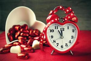 Valentinstag herzförmige rote Liebesuhr mit Pralinen foto