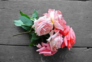 lebendiger Strauß rosa Rosen auf grauem rustikalem Holztisch