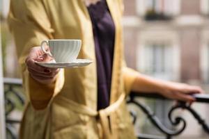 Frau, die Kaffee auf dem Pariser Balkon anbietet foto