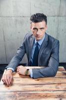 selbstbewusster Geschäftsmann, der am Tisch sitzt foto