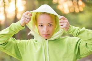 selbstbewusste sportliche Frau, die modischen grünen Kapuzenpulli trägt. foto