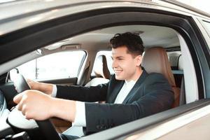hübscher junger Mann im Autohaus foto