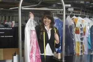 Besitzerin, die sauberes Kleid in der Wäsche hält foto