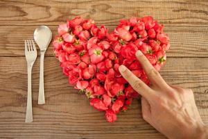 Herz aus roten Rosen im hölzernen Hintergrund, beim Mittagessen