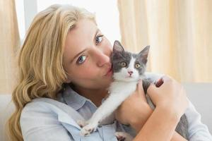 hübsche Blondine mit Haustierkätzchen auf Sofa foto