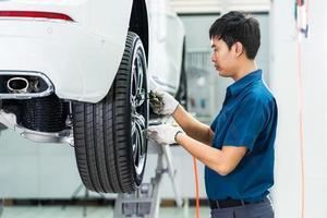 asiatischer Mechaniker, der Autoräder prüft foto