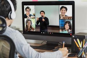 Rückansicht des asiatischen Geschäftsmannes, der über Videokonferenz arbeitet foto