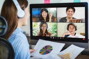 Rückansicht der asiatischen Geschäftsfrau, die über Videokonferenz arbeitet foto