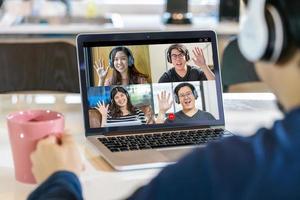 Rückansicht des asiatischen Geschäftsmannes auf Videoanruf mit Team