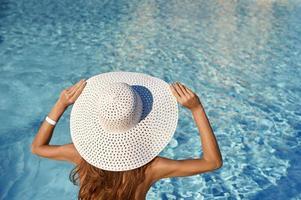 Rückansicht der Frau im weißen Hut, der nahe Pool an einem sonnigen Tag sitzt. Seereisekonzept mit Platz für Ihren Text