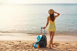 schöne junge Frau mit einem Hut, der am Strand steht