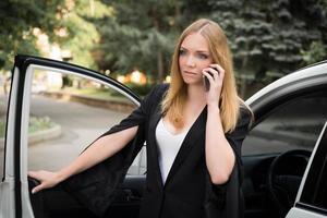 verärgerte junge Frau, die am Telefon spricht und aus dem Auto steigt foto