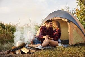 junges Paar, das durch Feuer auf Campingplatz ruht foto
