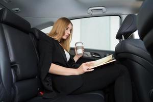 Frau mit Notizblock und Kaffee auf dem Rücksitz foto