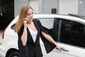 Frau spricht am Telefon und öffnet die Autotür