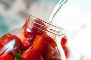 Tomaten werden beim Einmachen mit gekochtem Wasser überschwemmt. Dosen- foto