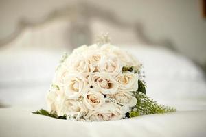 Blumenstrauß mit weißen Rosen, die auf einem Bett liegen foto