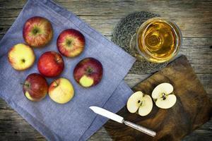 Stillleben-Komposition mit rotreifen Äpfeln und Saft. foto