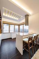 weiße moderne Küche mit Insel- und Barhockern
