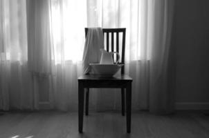 Stuhl mit Decke, Schüssel und Krug foto