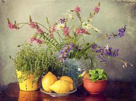 wilde Blumen in Vase, Kräutern und Zitronenfrüchten foto