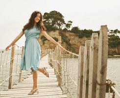junge glückliche Frau auf der Brücke nahe Meer