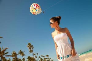 lächelnde schöne Frau beim Sonnenbaden am Strand foto