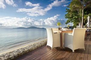 Tisch und Stühle am Meer foto