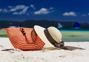 Hut und Tasche am tropischen Strand foto