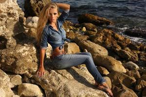 hübsches blondes Mädchen in der Jeanskleidung, die am Sommerstrand aufwirft