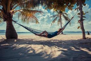 eine Frau in einer Hängematte, die sich am Strand entspannt
