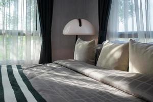 modernes Schlafzimmer mit Kissen und weißer Lampe
