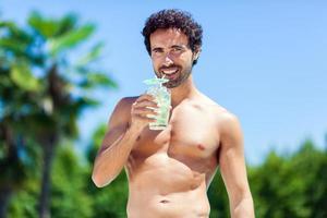 schöner junger Mann, der Cocktail in einem Schwimmbad trinkt foto