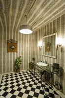 Spiegel und Waschbecken bei Licht über kariertem Boden