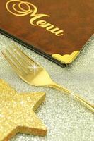 goldene Gabel und Restaurantmenü auf festlichem Hintergrund foto
