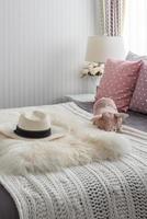 rosa Kissen mit rosa Puppe auf weißem Holzbett foto