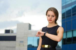 Geschäftsfrau schaut nachdenklich auf ihre Armbanduhr foto