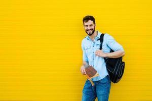 schöner Mann mit Rucksack auf gelb