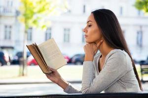 Frau liest Buch auf der Bank im Freien foto