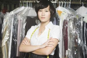 Frau mit verschränkten Armen stehend gegen Kleiderstange in der Wäsche foto