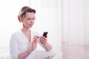 starke Frau liest Nachricht auf Smartphone foto