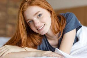 glückliche rothaarige Frau, die im Bett liegt foto