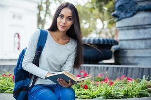 Studentin, die Buch hält und Kamera betrachtet foto