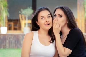 zwei beste Freundinnen flüstern ein Geheimnis