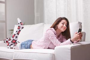 lustiges Lächeln eines Teenagers, der mit ihrem Handy eine SMS schreibt foto