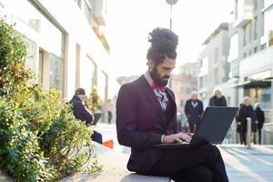 stilvoller eleganter Dreadlocks-Geschäftsmann mit Notizbuch foto