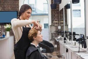 lächelnder Friseur im Chat mit Kunden foto